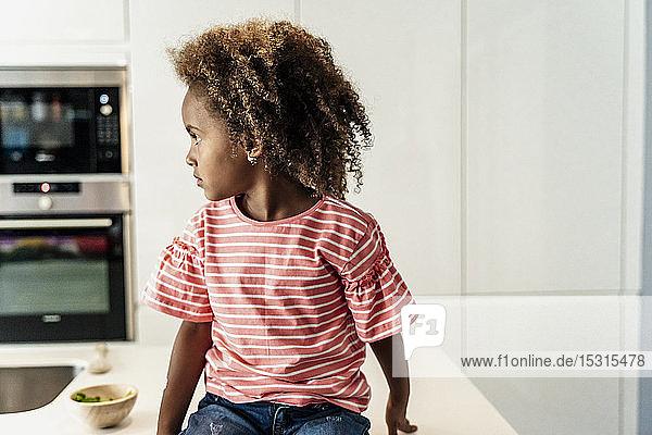 Girl sitting on kitchen counter looking sideways