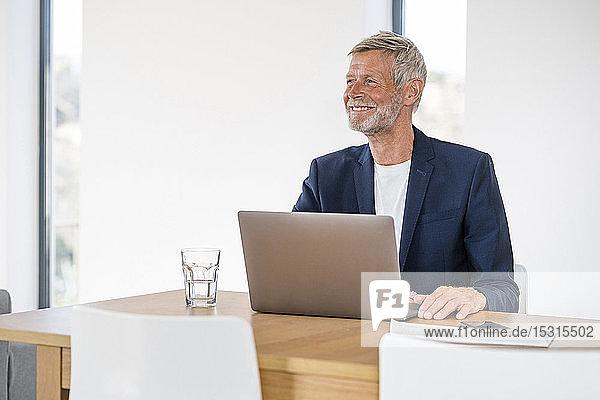 Smiling senior businessman with laptop sitting at desk at home