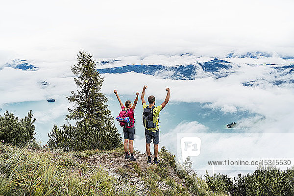 Happy young couple with raised arms on a hiking trip in the mountains  Herzogstand  Bavaria  Germany