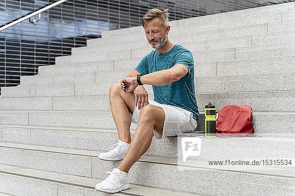 Sportlicher Mann prüft seine Smartwatch