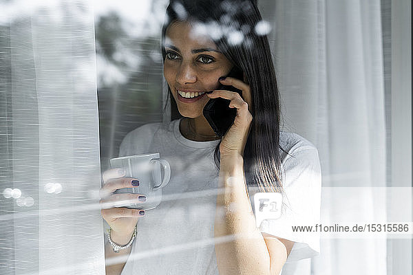 Smiling young woman on cell phone behind windowpane