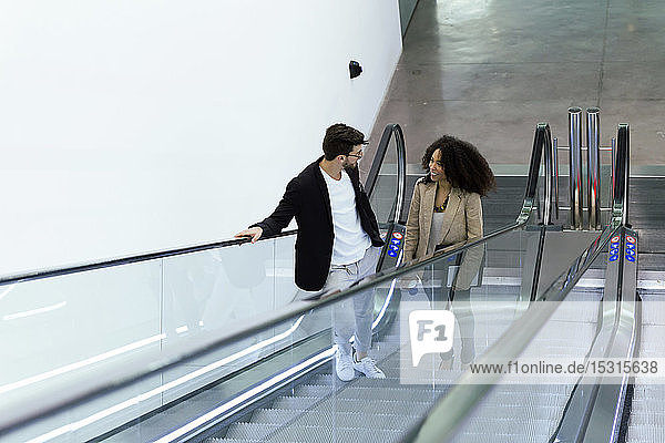Two young business partners talking on an escalator