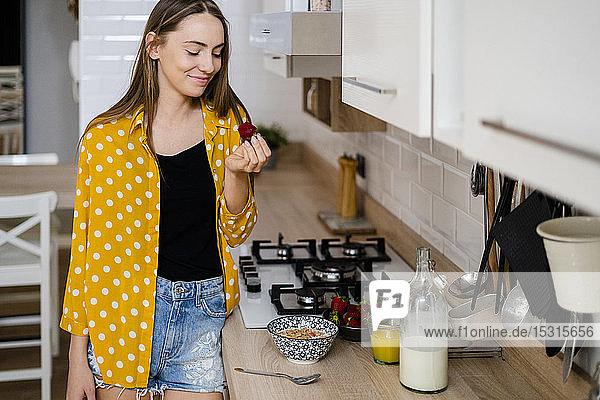 Junge Frau frühstückt zu Hause in der Küche