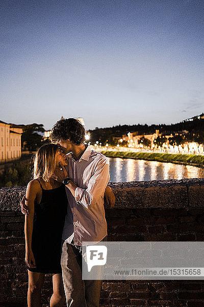 Zärtliches junges Paar küsst sich nachts auf einer Brücke  Verona  Italien