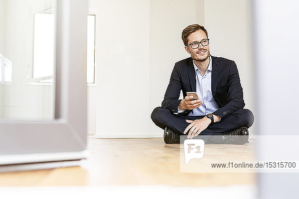 Smiling businessman sitting on the floor with cell phone