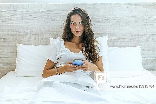 Porträt einer jungen Frau mit Handy im Bett zu Hause