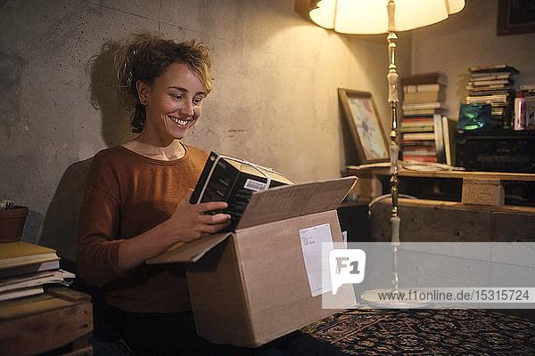 Lächelnde junge Frau packt Paket zu Hause aus