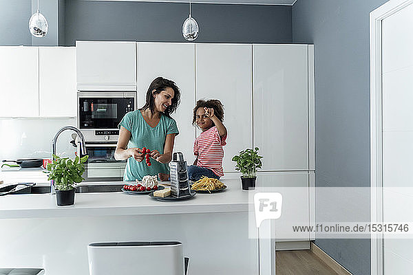 Mother and daughter cooking in kitchen together
