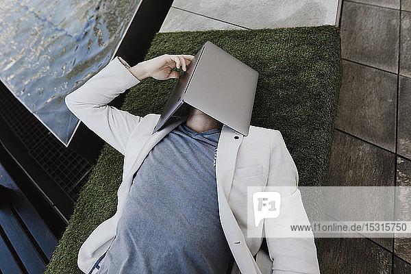 Junger Geschäftsmann entspannt sich auf Kunstrasen und bedeckt das Gesicht mit seinem Laptop