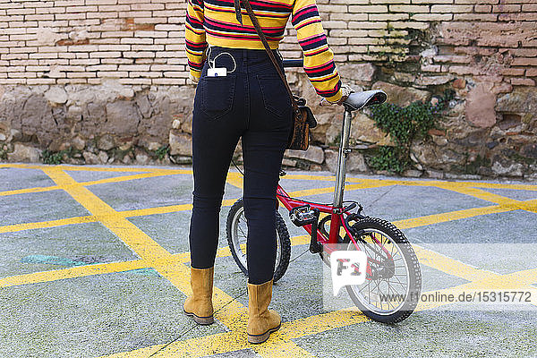 Woman with bicycle carrying smartphone in her pocket  partial view