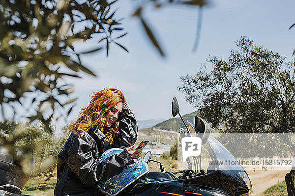 Redheaded woman on motorbike looking at cell phone  Andalusia  Spain