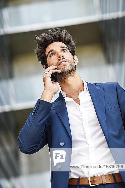 Geschäftsmann telefoniert vor einem Bürogebäude per Handy