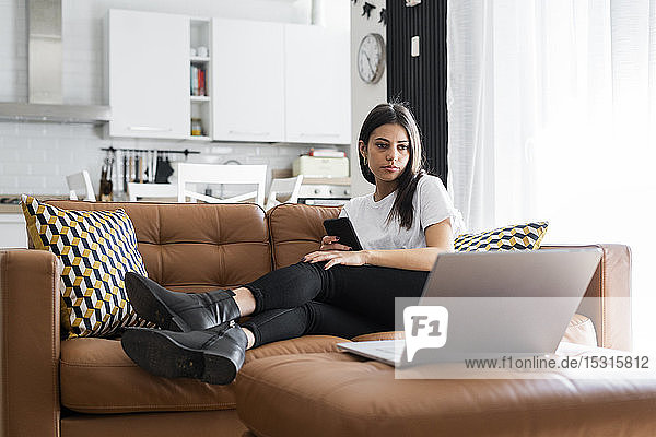 Young woman sitting on couch at home using laptop
