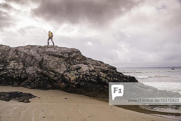 Frau in gelber Regenjacke am Felsstrand stehend