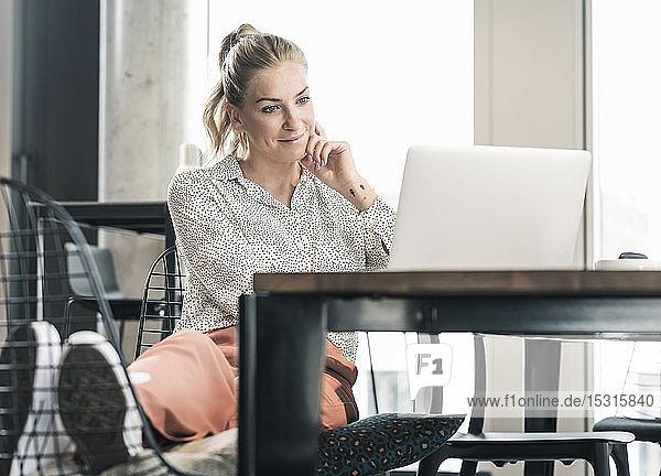 Geschäftsfrau  die im Büro am Tisch sitzt und einen Laptop benutzt