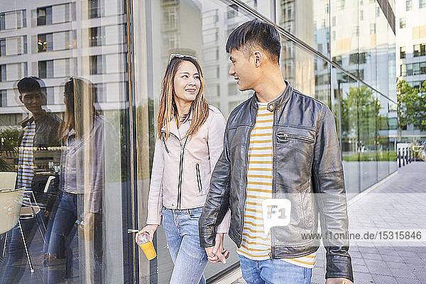 Paar in Lederjacken geht Hand in Hand in der Stadt