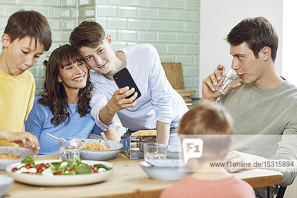 Mother and her four sons taking smartphone selfies at lunch