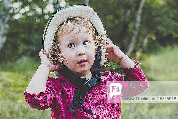 Portrait of toddler girl putting on oversized bicycle helmet