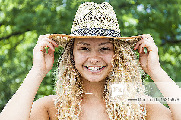 Portrait of smiling blond woman wearing straw hat,  hands on hat