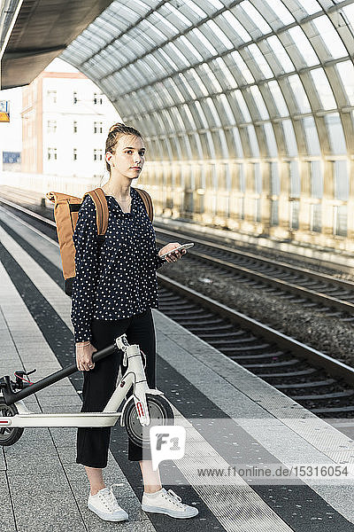 Young woman with electric scooter at the train station