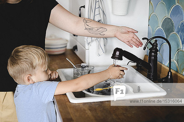 Little boy washing peach in the kitchen with his mother's help