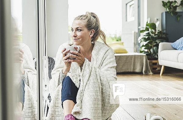 In eine Decke gehüllte Frau sitzt zu Hause am Fenster und trinkt Kaffee
