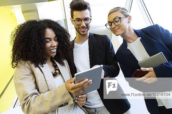 Lächelnde junge Geschäftsleute  die sich eine Tablette teilen