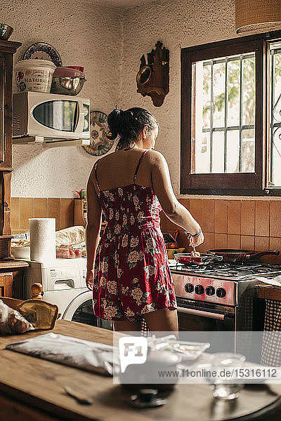Rückansicht einer Frau  die in der Küche mit einer Pfanne kocht
