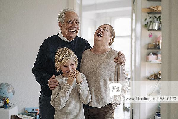 Lachende Großeltern mit Enkel zu Hause