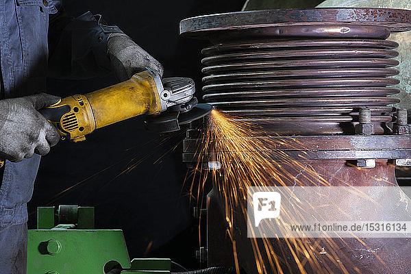 Nahaufnahme eines Arbeiters mit einem Winkelschleifer in einer Fabrik