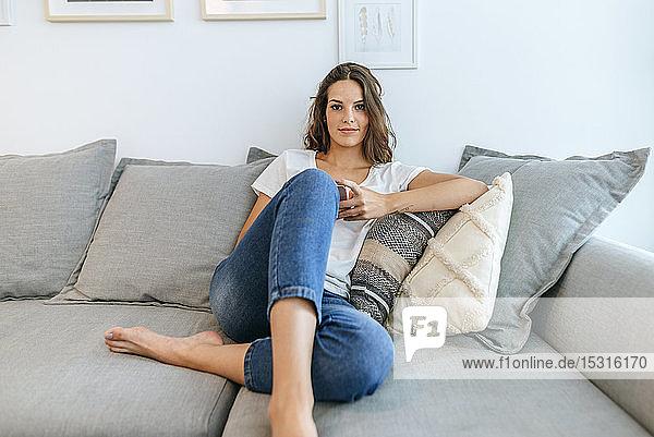 Porträt einer auf dem Sofa sitzenden jungen Frau mit Mobiltelefon