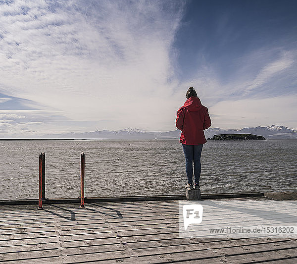 Young woman standig on a jetty  looking at the sea  South East Iceland