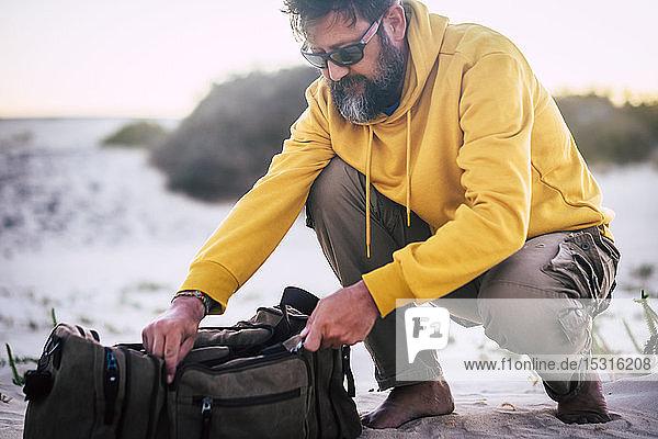 Mann mit gelbem Kapuzenpullover und braunem Korb am Strand
