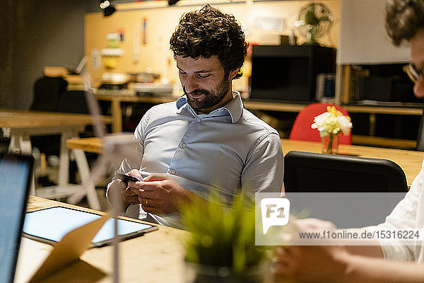 Businessman using cell phone at desk in office
