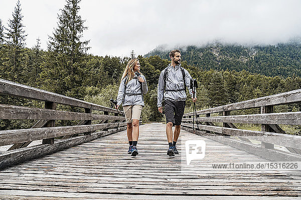 Young couple on a hiking trip walking on wooden bridge  Vorderriss  Bavaria  Germany