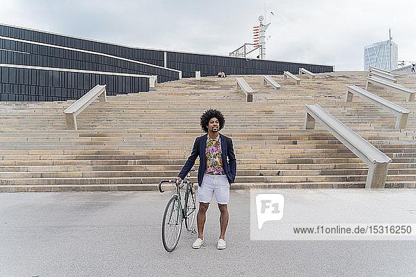 Stilvoller Mann mit Fahrrad an der Treppe stehend