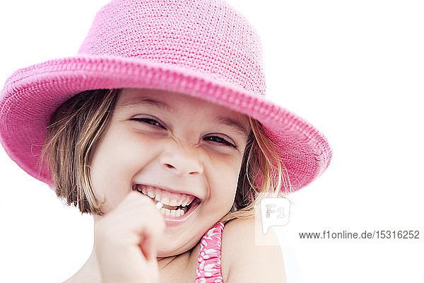 Portrait of happy girl with lollipop wearing pink hat in summer