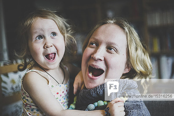 Portrait of mother and little daughter having fun together at home