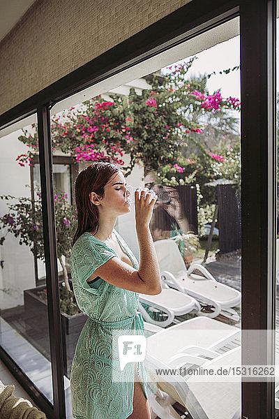 Junge Frau trinkt Wasser in einem Kurort