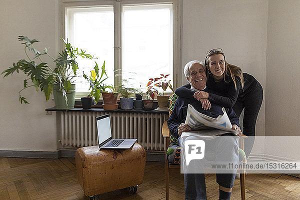 Porträt einer glücklichen jungen Frau und eines älteren Mannes mit Zeitung zu Hause