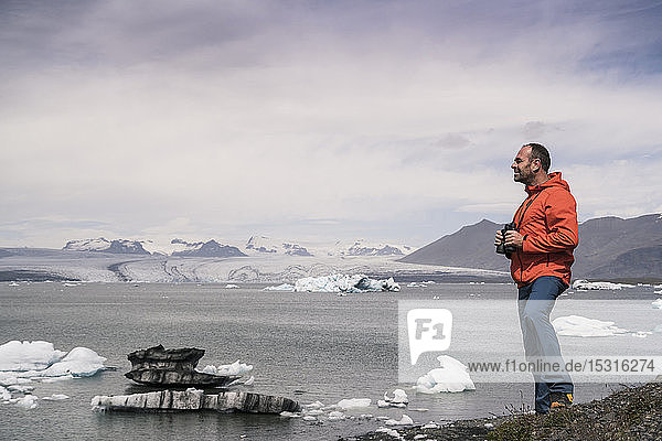 Erwachsener Mann beobachtet den Vatnajokull-Gletscher mit einem Fernglas  Island