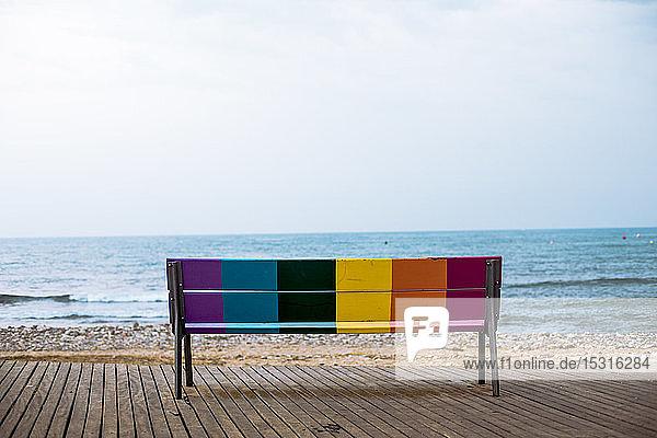 Rückansicht einer bunten Bank  die vor dem Meer steht  Spanien