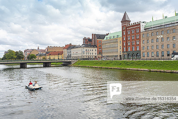 Freunde segeln im Tretboot auf dem Kanal bei Gebäuden in der Stadt Malmö
