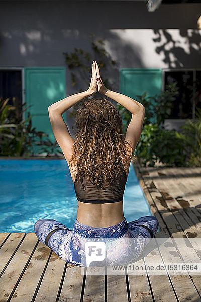Rückansicht einer Yoga praktizierenden Frau am Pool  Costa Rica