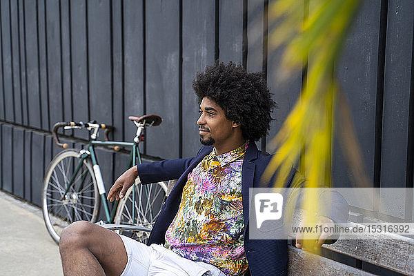 Stilvoller Mann mit Fahrrad auf einer Bank sitzend
