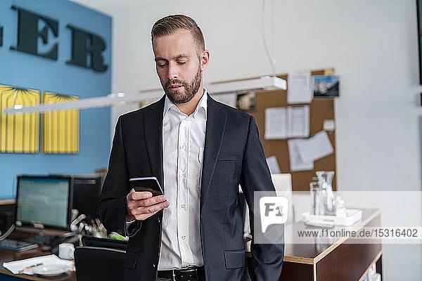 Seriöser Geschäftsmann benutzt Mobiltelefon im Büro