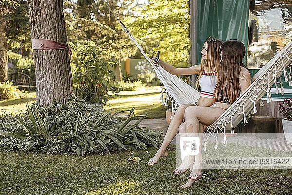 Zwei junge Frauen sitzen auf einer Hängematte im Garten und nehmen Selfie mit dem Handy