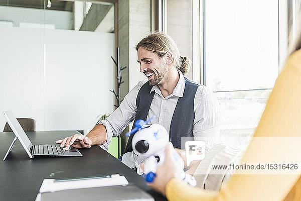 Glücklicher junger Geschäftsmann und Geschäftsfrau sitzen am Schreibtisch im Büro