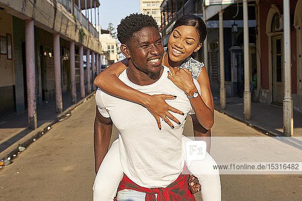 Junger Mann trägt seine Freundin huckepack auf der Straße  Mabuto  Mosambik
