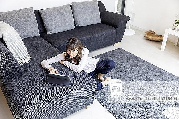 Entspannte Frau benutzt Tablette im Wohnzimmer zu Hause